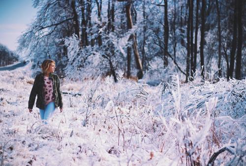 Femme marchant dans un paysage givré près d'un bosquet d'arbres